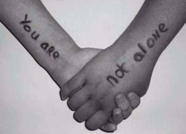Holding hands with You Are not alone written on the arms